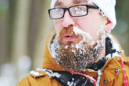 Portrait of a young man in glasses clouded over with frost on the beard and moustache in cold weather, close-up on blurred background Foto de archivo