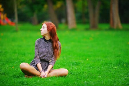 Portrait of young calm long-haired girls brown-haired women in short dress sitting in a Lotus position on a green lawn in a Park on a clear Sunny day. Stock Photo