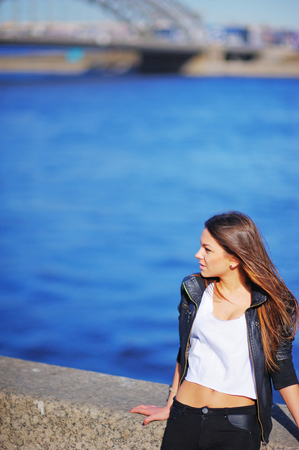 Portrait profile of young beautiful woman with tousled in the wind long hair, standing on the waterfront on the background the blue waters of the Neva. Stock Photo