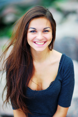 Portrait of a smiling beautiful long-haired brunette woman in a black t-shirt with a deep neckline with a blur effect in the background, closeup