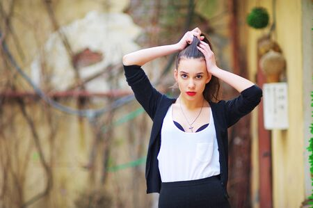 beautiful girl with long hair in a white shirt and a black cardigan gathers her hair in a ponytail