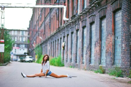 Young beautiful long-legged girl athletic sits on the twine on the street at the urban building background