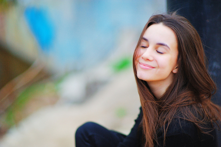 Portrait of a dreamy beautiful woman on the street with your eyes closed and a cute smile, on blurred background, close up. Stock Photo