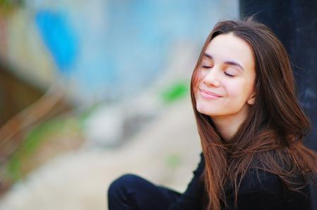 Retrato de una hermosa mujer de ensueño en la calle con los ojos cerrados y una linda sonrisa, sobre fondo borroso, de cerca. Foto de archivo