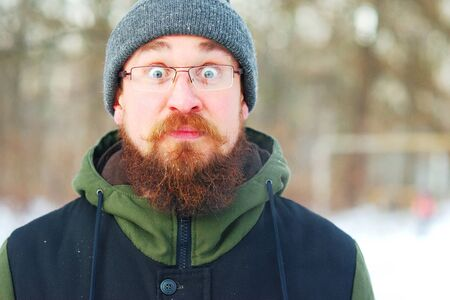 young bearded guy with glasses and warm winter clothes stared in surprise