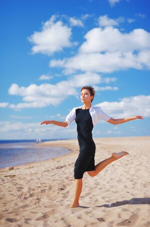 blue background: Young slim woman dancing barefoot on the sandy shores on the background beautiful white clouds on blue sky.