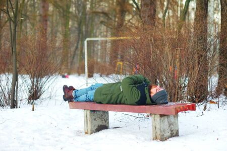 tired: Tired bearded man with glasses, lying on a snowy bench, ignoring the cold, in a city Park in the winter.