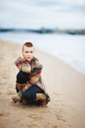 Beautiful, confident, girl with short hair squatted on the banks of the Neva. The concept of youth fashion