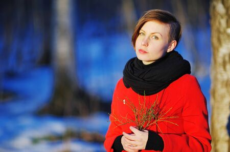 Portrait of calm beautiful woman in a red coat with a green twig in the hands of a walk in winter Park at sunset on blurred background, close up.