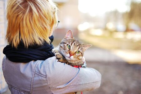 blonde girl with a cat in her arms on a city street on a Sunny day Stock Photo
