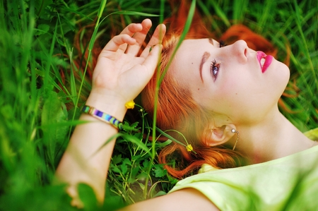 Young beautiful redheaded woman, eyes closed, resting in the Park, lying in the meadow among the beautiful wildflowers.