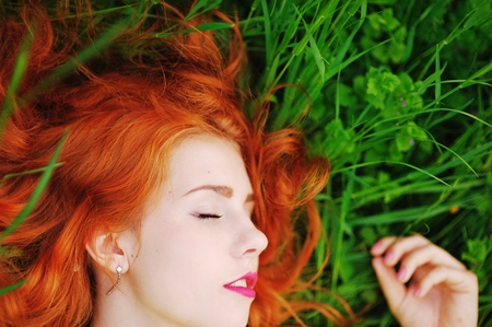 head is a beautiful red-haired girl had fallen asleep on the green grass on lawn, close-up