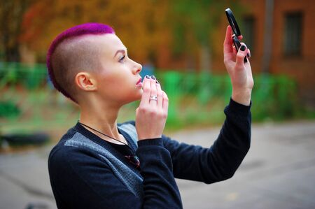 Charming young girl with short pink hair, punk-inspired looks in the mirror and applies her makeup with a sponge while walking around city Stock Photo