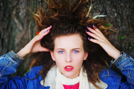 blue background: portrait of a delightful girl whose hair lie on a big tree. Her eyes is shrill