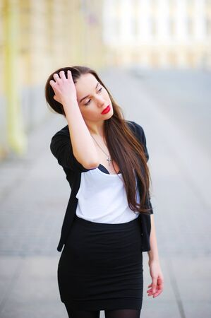 beautiful girl with long hair in a white shirt and a black cardigan straightens her hair