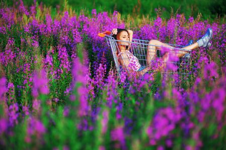 Beautiful dark-haired girl student in a t-shirt and short shorts got in the cart from the store in the middle of a clearing beautiful flowers of fireweed, quietly enjoying the sun on her face.