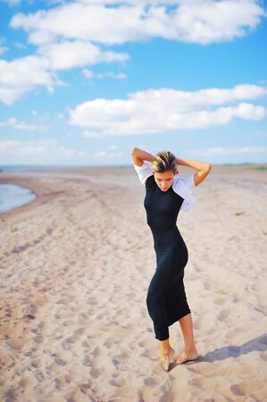 Portrait of a young slender girl model in black dress posing barefoot on a sandy beach on the seafront on a Sunny day for advertising in a fashion magazine. Stock Photo