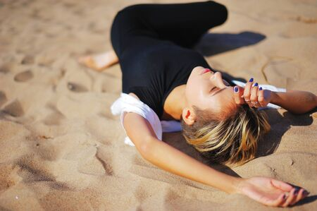 Pretty young girl relaxing lying on the sand, his hands behind his head