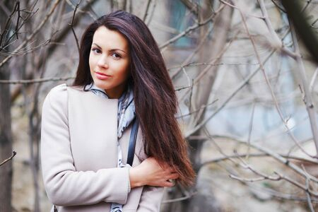 Portrait of a pretty long-haired girl brunettes with beautiful brown eyes in an elegant coat on a blurred background of tree trunks and bare branches, closeup.