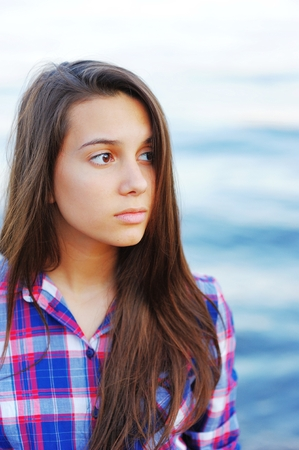 Portrait of a young handsome long-haired girl with sad eyes in a plaid shirt against a blue blurred background surface of river, closeup Stock Photo