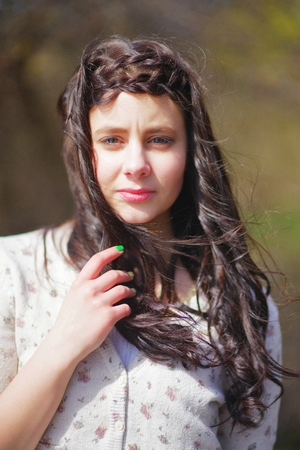 Portrait of a beautiful young girl closeup. Beautiful attentive eyes look soulful. A little windswept silky long hair. Stock Photo
