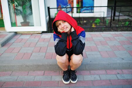 Portrait of a young smiling girl in a sports jacket with a hood, sitting on the steps of porch of a small shop, elbows on bare knees.