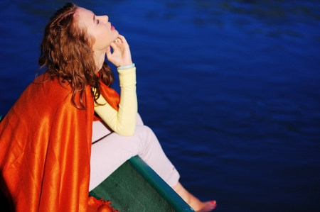 young beautiful woman sitting on the edge of the boat lowered feet in the water turned orange blanket. She clothing