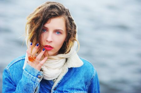 blue background: girl in a denim jacket with wet hair on the background of the river Stock Photo