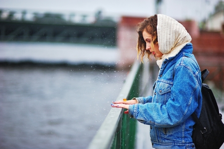 Girl on the quay in the rain beats hands on the railing forming splashes