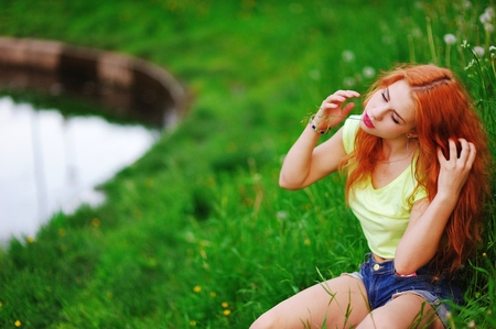 Wonderful portrait of a beautiful redheaded woman resting on the shore of the lake in the summer. Girl sitting on green grass, with downcast eyes and corrects unruly, wavy hair.