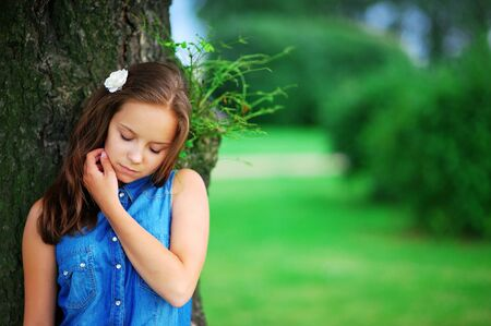 Portrait of pensive beautiful woman with closed eyes leaning against a great tree in a summer Park on blurred background, close up. Stock Photo