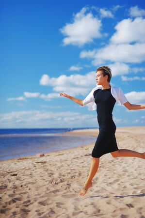 blue background: Wonderful portrait of a young slim woman in a black dress with a white Bolero, running barefoot on the sand to the sea on the background of blue sky and white clouds of air.