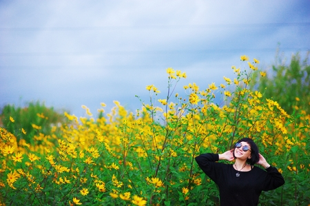 Portrait of young beautiful smiling brunette girl with stylish haircut in a black jumper wearing sunglasses in the field, among yellow flowers of Jerusalem artichoke. Stock Photo