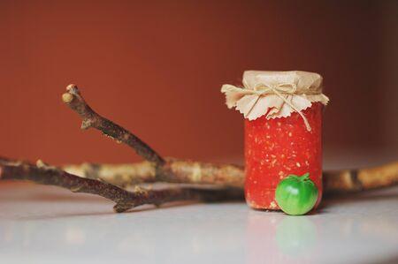 Jar with a sauce of fresh tomatoes horseradish and garlic. Autumn harvesting. Close-up.