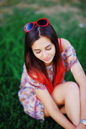 Wonderful portrait of fashion charming smiling girl with drooping long eyelashes with bright red tress hair sitting on the grass in the summer Park on blurred background, close-up