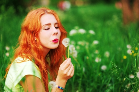 Portrait of young pretty happy red-haired girl sitting on the green lawn and blowing on a dandelion enjoying summer sun Stock Photo