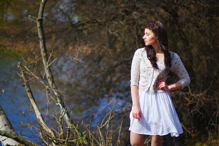 Portrait of a dreamy pretty woman a white short dress, meditating with closed eyes on the lake in bushes.