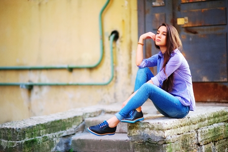 pensador: brunette girl sitting in a blue shirt with stripes and jeans in the city Foto de archivo