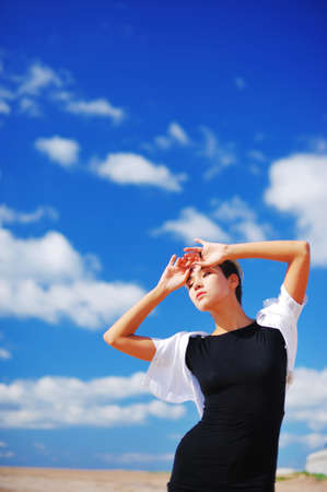 Portrait of a pensive beautiful woman with lifted hands against blue sky with floating white clouds, close-up Stock Photo