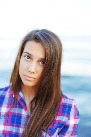 Portrait of cute long haired girls brunette with beautiful brown eyes in a plaid shirt on a Sunny day closeup on a blurred background of the sea