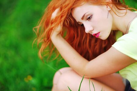 brooding: Young attractive red-haired girl with pensive look sitting on the grass, leaning on his knees and adjusting his hair in the summer Park, side view closeup.