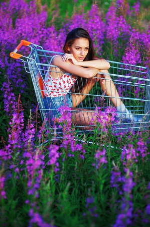 teeny: Portrait beautiful pensive long-haired brown-haired woman posing in supermarkets trolley in a flowered field. Girl dressed in a white t-shirt and shorts sitting under bright sun, among purple flowers of fireweed