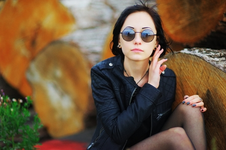 Beautiful young girl with sunglasses in a black jacket sitting on logs in an industrial area on the outskirts of the city. Her glasses reflected the cloudy sky. Street style clothing. Stock Photo