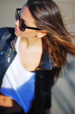 portrait of a young beautiful girl in sunglasses and a black jacket with long silky hair fluttering with the wind on the gray background, blurred focus, close up.