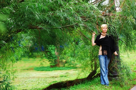 Young pretty blonde girl in blue jeans and a black tippet stands near the willow in the summer.