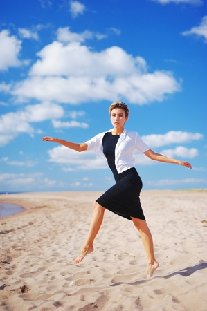 blue background: Portrait of a sad slender young woman with short hair, with outstretched hands, Bouncing on the sand, on blurred blue sky background
