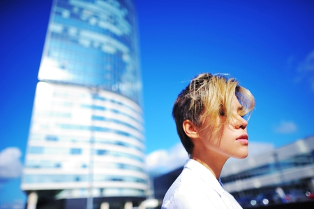 blue background: Portrait of modern business woman around a multi-storey office building in the cityscape on the background of beautiful blue sky.