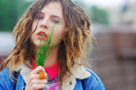 blue background: Young charming girl with dreads with a bunch of grass in his hands in a city Park on a bright day.