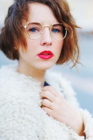 blue background: Wonderful portrait of cute charming girl with beautiful eyes and round glasses with her mouth slightly open in a white cardigan on blurred background, closeup. Stock Photo