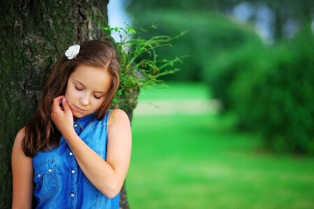 Portrait of beautiful smiling young women in blue denim shirt with flower in her hair, to relax, leaning against the tree, calm and dream with closed eyes in a Park on blurred background of grass and shrubs Stock Photo